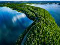 Aerial view of road with cars between green forest and blue lake water in Finland - PhotoDune Item for Sale