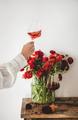 Womans hand with rose wine in glass and red flowers - PhotoDune Item for Sale