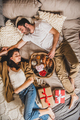 Happy smiling couple lying in bed and having festive breakfast - PhotoDune Item for Sale