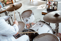 Close up of caucasian musician playing drumms during online concert with the band at home isolated - PhotoDune Item for Sale