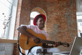 African-american musician playing guitar during online concert at home isolated and quarantined - PhotoDune Item for Sale