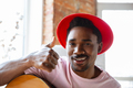 African-american musician in red hat greeting audience before online concert at home isolated and - PhotoDune Item for Sale