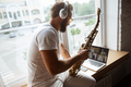 Caucasian musician playing saxophone during online concert at home isolated and quarantined - PhotoDune Item for Sale