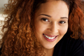 Close up beautiful mixed race woman with curly hair smiling - PhotoDune Item for Sale