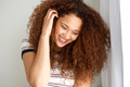 young woman smiling with hand in hair - PhotoDune Item for Sale