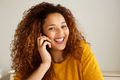 Close up happy young mixed race woman smiling and talking on cellphone - PhotoDune Item for Sale