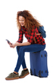 happy young female traveler sitting on suitcase and looking at mobile phone - PhotoDune Item for Sale