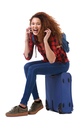 happy young woman talking on mobile phone while sitting on suitcase by isolated white background - PhotoDune Item for Sale