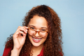 Close up woman with curly hair and glasses smiling against blue background - PhotoDune Item for Sale