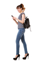 side portrait of young woman walking with mobile phone and bag against white background - PhotoDune Item for Sale