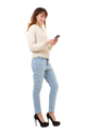Full length smiling young woman holding cellphone against isolated white background - PhotoDune Item for Sale