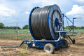 Irrigation sprinkler and rolled hose.  Watering concept. - PhotoDune Item for Sale