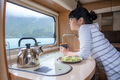 Woman in the interior of a camper RV motorhome with a cup of coffee looking at nature. - PhotoDune Item for Sale