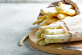 Freshly picked raw organic white asparagus bundles on a wooden board on a light grey stone - PhotoDune Item for Sale