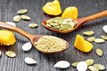 Flour and seeds pumpkin in spoons on dark board - PhotoDune Item for Sale