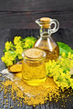 Oil mustard in jar and decanter with flower on dark wooden board - PhotoDune Item for Sale