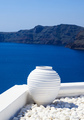 Santorini, Greece. White terrace with ceramic pot and pebbles against blue sea and sky background. - PhotoDune Item for Sale