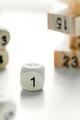Number one on the face of wooden dice cube on a light grey background with blurred piramyd from - PhotoDune Item for Sale