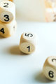 Wooden cubes with numbers on a light grey background. Dice game concept - PhotoDune Item for Sale