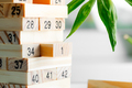 Wooden creative constructor from blocks with numbers against light background. Jenga game for - PhotoDune Item for Sale