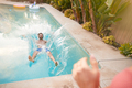 Hispanic Couple With Woman Pushing Man Into Swimming Pool At Outdoor Summer Party - PhotoDune Item for Sale