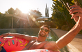 Man Floating On Inflatable Ring At Summer Pool Party Taking Selfie On Mobile Phone - PhotoDune Item for Sale