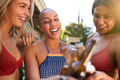 Group Of Female Friends Outdoors Drinking Beer And Making Toast As They Enjoy Summer Pool Party - PhotoDune Item for Sale
