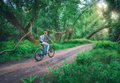 Woman riding a bicycle in forest in spring at sunset - PhotoDune Item for Sale
