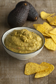 Bowl guacamole with tortilla chips and avocado in the background - PhotoDune Item for Sale