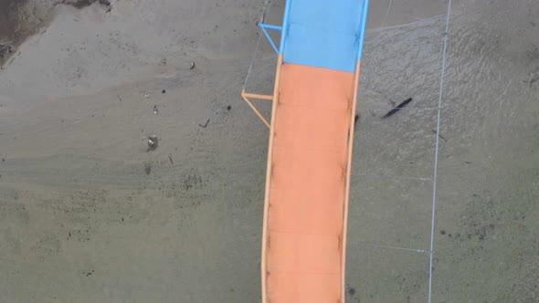 Aerial top view of a bright colored pedestrian bridge