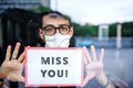Portrait of sad man with face mask holding miss you sign, quarantine and lockdown concept - PhotoDune Item for Sale