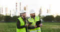 Two young engineers with tablet standing outdoors by oil refinery, discussing issues - PhotoDune Item for Sale