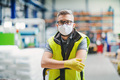 Man worker with protective mask standing in industrial factory or warehouse - PhotoDune Item for Sale