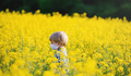 Side view of small boy with face mask standing in nature in rapeseed field - PhotoDune Item for Sale