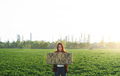 Young woman activist with placard standing outdoors by oil refinery, protesting - PhotoDune Item for Sale