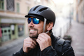 Delivery man courier fastening bicycle helmet and sunglasses in town - PhotoDune Item for Sale