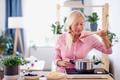 Senior woman cooking in kitchen indoors, stirring pasta in pot - PhotoDune Item for Sale