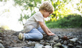 Side view of small boy playing with rocks and mud in nature - PhotoDune Item for Sale