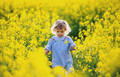 Front view of happy small toddler girl walking in nature in rapeseed field - PhotoDune Item for Sale