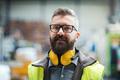 Technician or engineer with protective headphones standing in industrial factory - PhotoDune Item for Sale