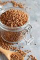 Raw dry buckwheat grain  in a jar with a spoon - PhotoDune Item for Sale