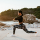 sexy athletic woman stretching exercises on beach at sunset