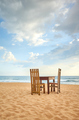 Wooden table and two chairs on a beach. - PhotoDune Item for Sale