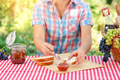 A woman in a plaid shirt spreads jam on bread - PhotoDune Item for Sale