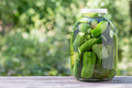 Canned homemade cucumbers in glass jar on wooden table - PhotoDune Item for Sale
