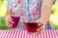 Female hands hold glass with grape or other red juice - PhotoDune Item for Sale