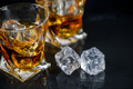 Glass of whiskey with cube ice on black background - PhotoDune Item for Sale