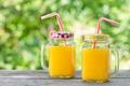 Orange juice in mason jars with straws on wooden table - PhotoDune Item for Sale