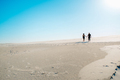 young couple a guy and a girl with joyful emotions in black clothes walk through the white desert - PhotoDune Item for Sale