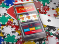 Online casino. Slot machine on smartphone screen, dice, casino chips and cards. - PhotoDune Item for Sale